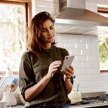 Woman using phone in kitchen.